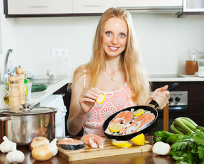 woman cooking salmon  with lemon on  pan