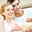 Couple eating popcorn and watching TV