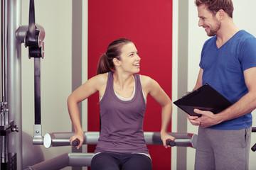 trainer mit einer sportlerin im fitness-studio