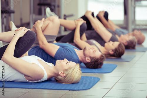 Leinwanddruck Bild gruppe macht dehnübungen im fitness-center