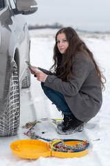 Femme mettant des chaînes sur la voiture de pneus neige d'hiver