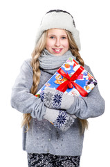 Teen girl with braids in warm hat and mittens keeping the gift