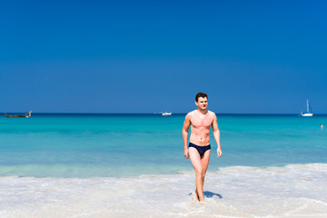 Young man walking out of the water in a tropical beach