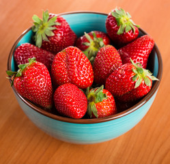 Strawberries in a Bowl, ona a wooden background