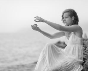 Woman holding zen stones in hand.