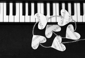 Piano keys and hearts of the music on a black background