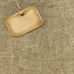 Old tag on fabric background