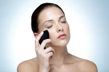 Attractive woman cleaning face with spa stone