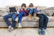 Brothers And Sister Using Technologies On Sofa
