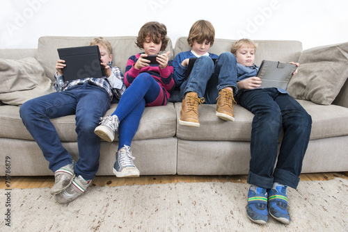 Brothers And Sister Using Technologies On Sofa - 75786879