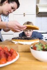 Boy Looking At woman Preparing Cake