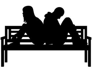 Sad couple sitting on a park bench