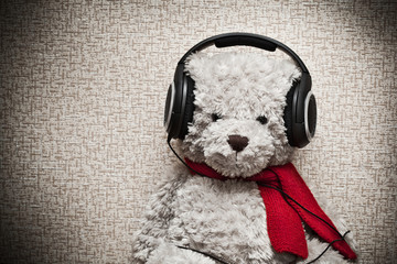 Teddy bear with headphones and a red scarf