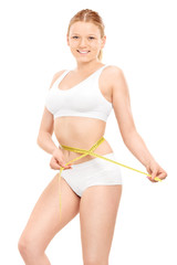 Blond girl in underwear measuring her waist