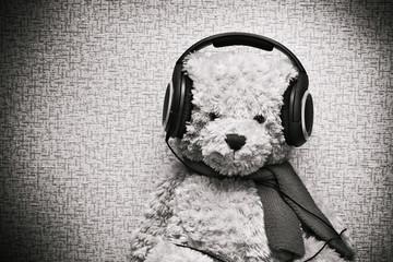 Plush teddy bear listening to music on headphones. Vintage