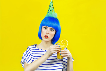 girl in a blue wig holding a glass juice on a colored background