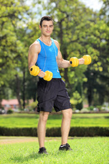 Young guy training with two dumbbells in a park