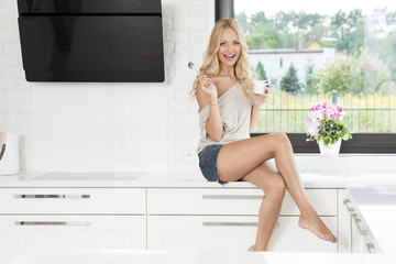 sexy woman sitting near window , in kitchen smiling