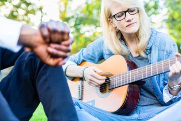 Junge Leute mit Gitarre machen Musik im Park