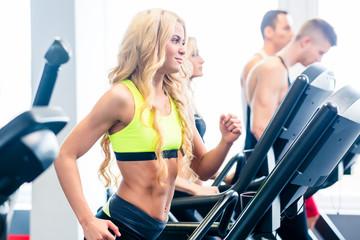 Gruppe auf Laufband beim Jogging im Fitnessstudio