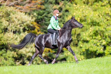Young girl riding a black horse in autumn time near forest.