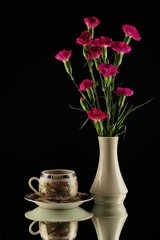 Purple carnations in white vase and turkish coffe cup