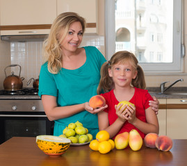 Woman and child in the kitchen with different kinds of fruits