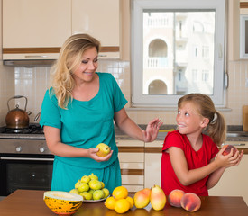 Healthy eating. Woman and girl in kitchen. Different fruits