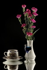 Purple carnations in white vase and coffe cup