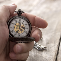 hands with vintage pocket watch