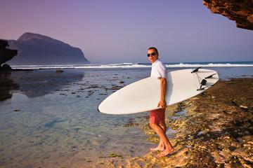 Man surfer with surfboard on a coastline. Bali. Indonesia