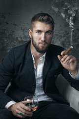 Attraktiver Mann mit Bart, Zigarre und  Whiskey