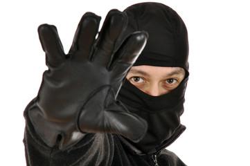 Einbrecher trägt Sturmhaube und Lederhandschuhe