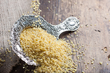 bulgur pours into the openwork silver spoon on dark background