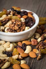 Assorted nuts in white bowl on wooden background.