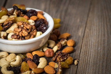 Assorted nuts in white bowl on wooden table.
