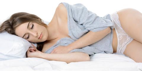 Frau in Unterwäsche schläft im Bett