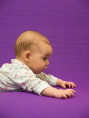 The infant tries to crawl.