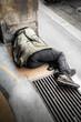 senzatetto sdraiato per terra che dorme - 75804217
