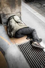 senzatetto sdraiato per terra che dorme
