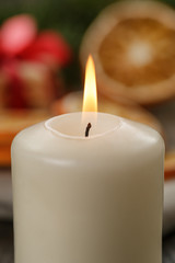 burning candle in front of christmas table