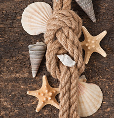 starfish, seashells and rope on old wooden background