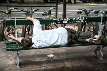senzatetto ubriaco sdraiato su una panchina