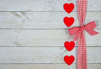 Schleife mit roten Herzen auf Holz Hintergrund
