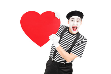 Mime artist holding a big red heart