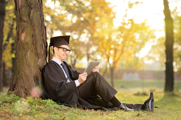 Man in graduation gown working on a tablet in park