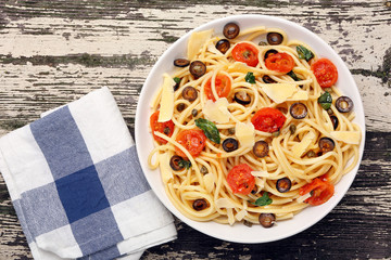 Spaghetti with olive sauce on wooden background