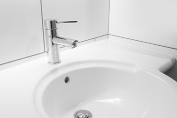 Faucet and white basin in a bathroom