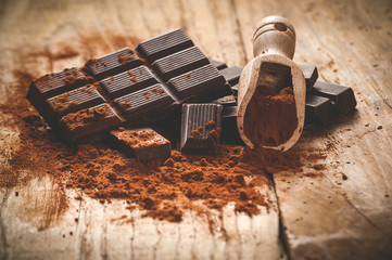 Noble dark chocolate on a wooden table in vintage style.