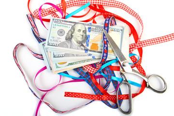 Hundred-dollar bills lying on a pile of gift ribbons.
